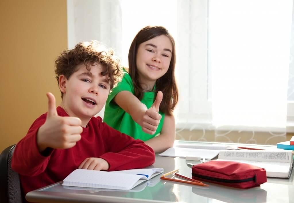 niños haciendo deberes pulgar ok